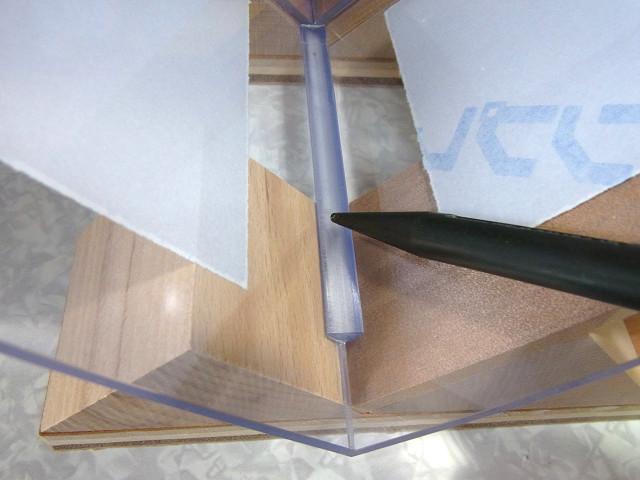 接着剤を流し込んだ塩ビ三角補強棒を軽く押さえる